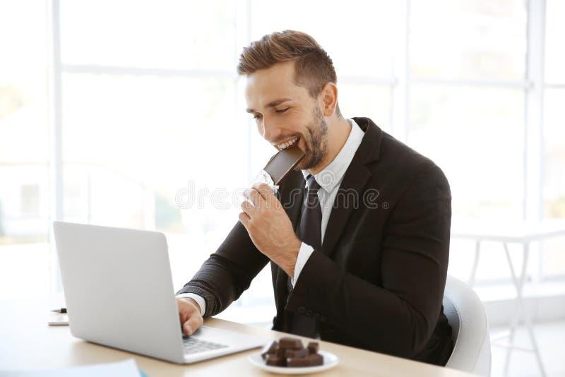 Junge Fleisch fressende Schokolade beim Arbeiten mit Laptop stockbilder