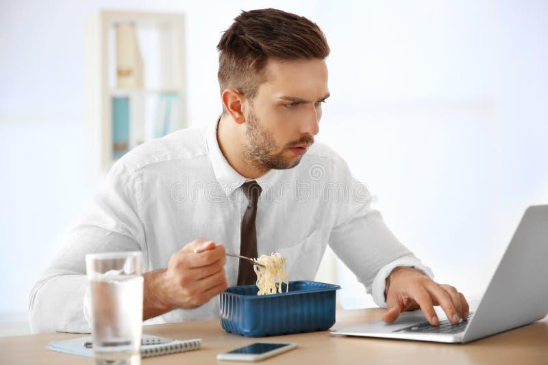 Junge Fleisch fressende sofortige Nudeln beim Arbeiten mit Laptop stockbild