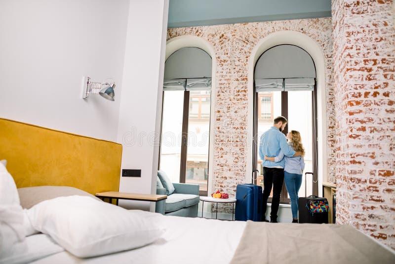 Junge, fröhliche Paare, die in einem Hotelzimmer mit großen Koffern ankommen, Rückblick stockfotografie