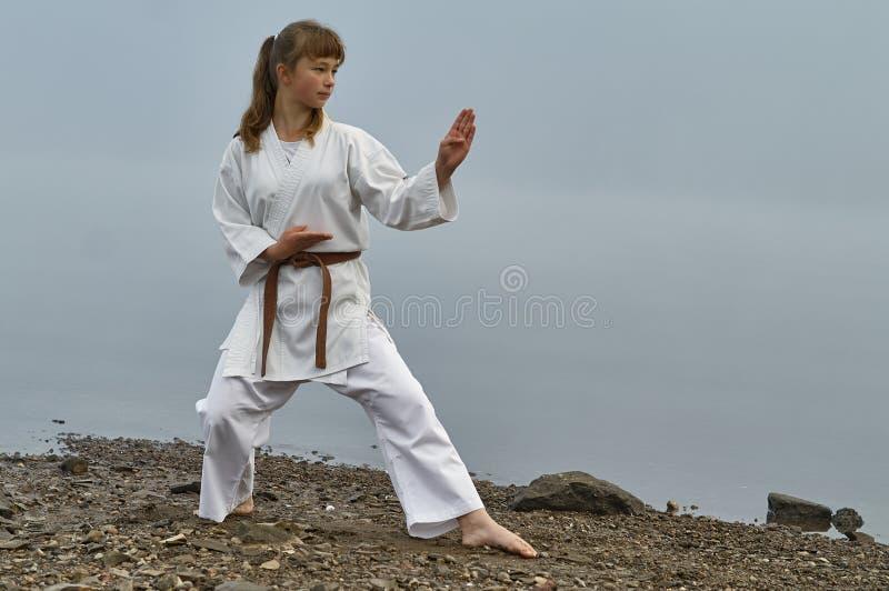 Junge Frau in übendem Karate des Kimonos auf Flussküste stockfoto