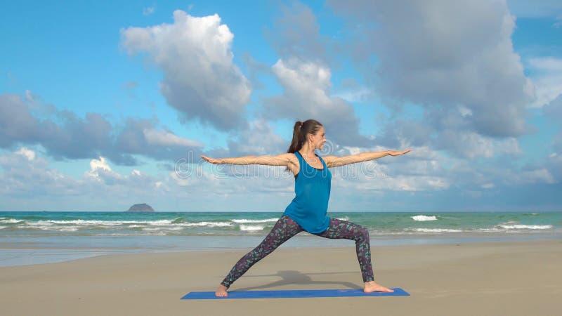 Junge Frau übt Yoga auf einem Strand bei Sonnenaufgang Gesunder Lebensstil stockbilder