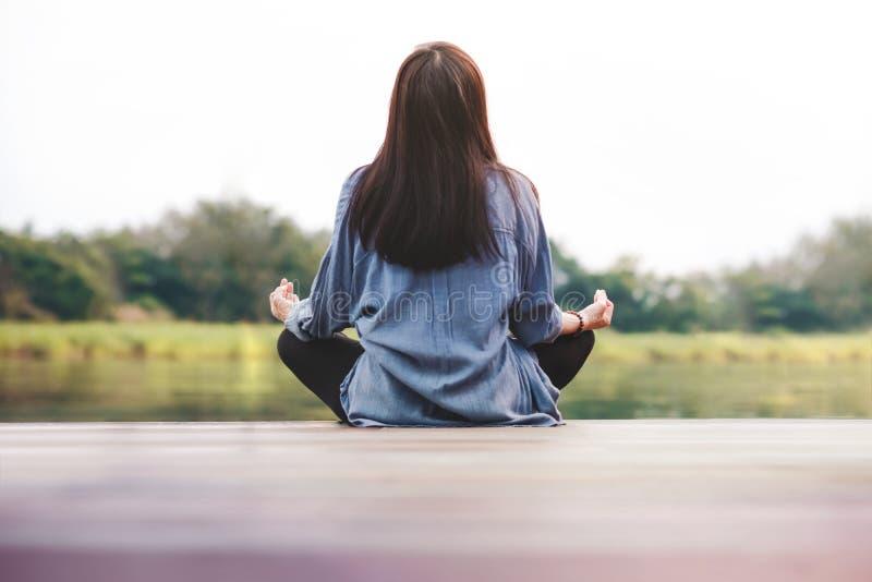 Junge Frau übt Yoga in im Freien Sitzen in Lotussitz Getrenntes Leben-und der psychischen Gesundheit Konzept stockfotografie