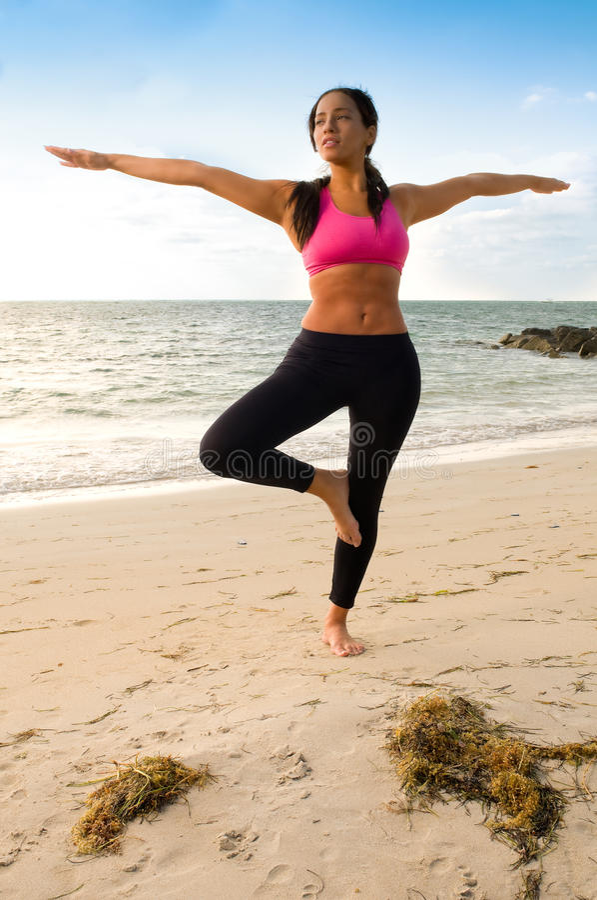 Junge Frau übt Yoga im Strand stockfotografie
