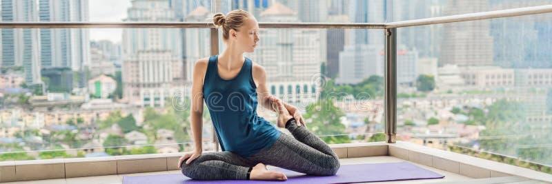 Junge Frau übt Yoga morgens auf ihrem Balkon mit einem Panoramablick der Stadt und der Wolkenkratzer FAHNE, langes Format stockbild