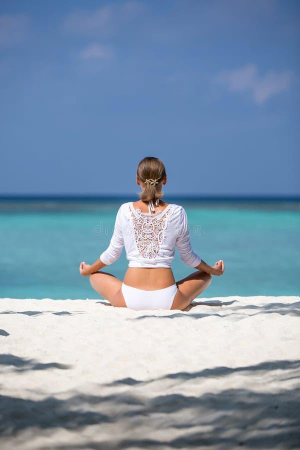 Junge Frau übt Yoga und meditiert im Lotussitz auf dem Strand lizenzfreie stockfotos