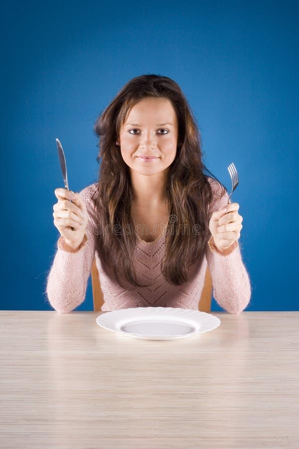 Junge Frau am Abendtische mit Gabel und Messer stockfotos