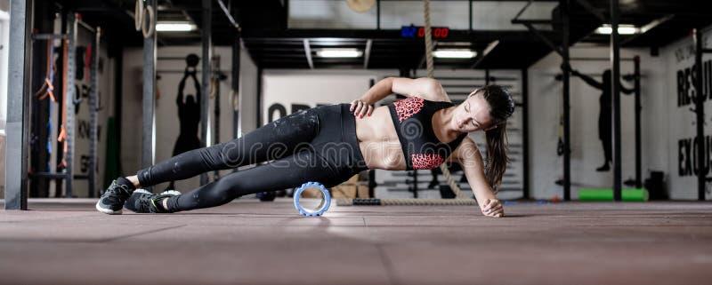Junge Frau arbeitet auf Turnhallenboden aus stockbilder