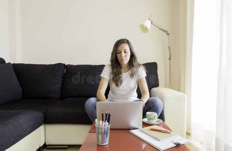 Junge Frau arbeitet zu Hause stockbilder