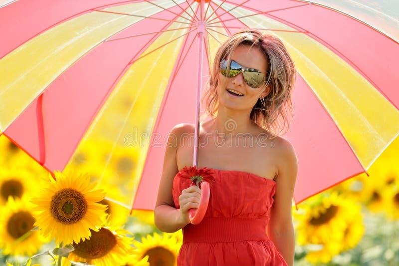 Junge Frau auf blühendem Sonnenblumefeld lizenzfreie stockfotografie