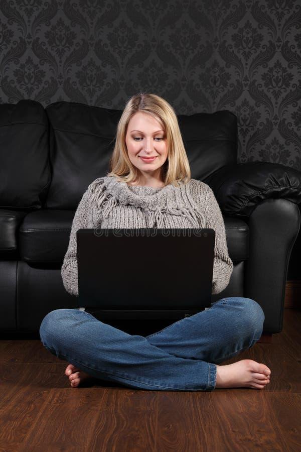 Junge Frau auf dem Fußboden zu Hause, der Internet surft lizenzfreies stockfoto