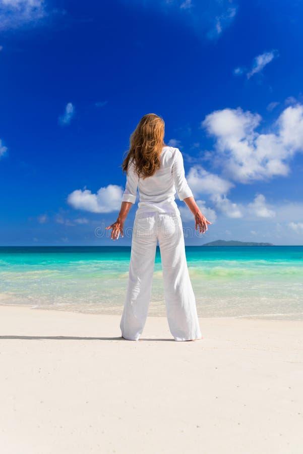 Junge Frau auf dem Sand nahe dem Ozean lizenzfreies stockfoto