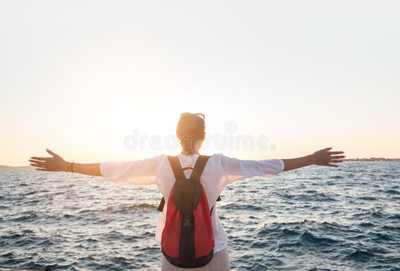 Junge Frau auf dem Strand am Sonnenuntergang stockbilder
