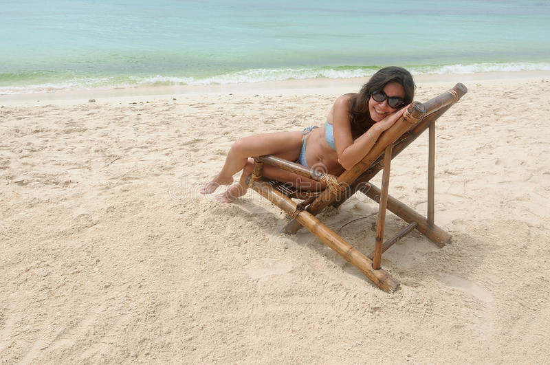 Junge Frau auf dem Strandstuhl auf Ufer stockbilder
