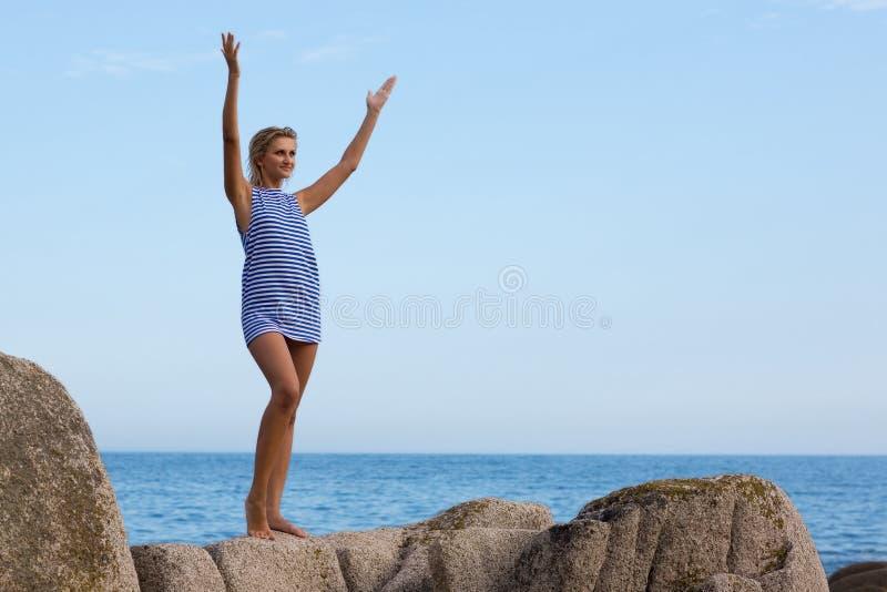 Junge Frau auf einem Felsen durch das Meer. stockfoto
