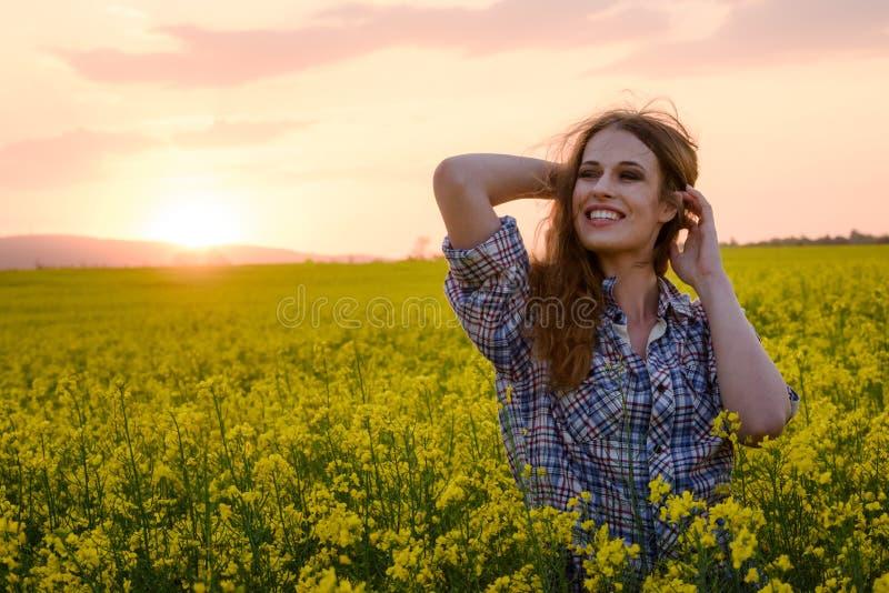 Junge Frau auf einem Gebiet des Ölrapssamens in der Blüte im Sonnenuntergang Freiheits- und Ökologiekonzept lizenzfreie stockfotografie