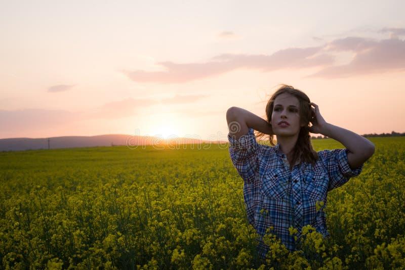 Junge Frau auf einem Gebiet des Ölrapssamens in der Blüte im Sonnenuntergang Freiheits- und Ökologiekonzept stockbild