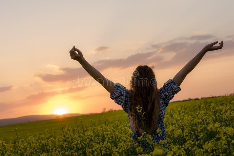 Junge Frau auf einem Gebiet des Ölrapssamens in der Blüte im Sonnenuntergang Freiheits- und Ökologiekonzept lizenzfreie stockbilder