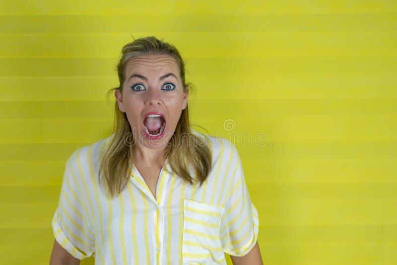 Junge Frau auf einem gelben Hintergrund mit Überraschungsausdruck und aufgeregtem Gesicht lizenzfreie stockfotografie