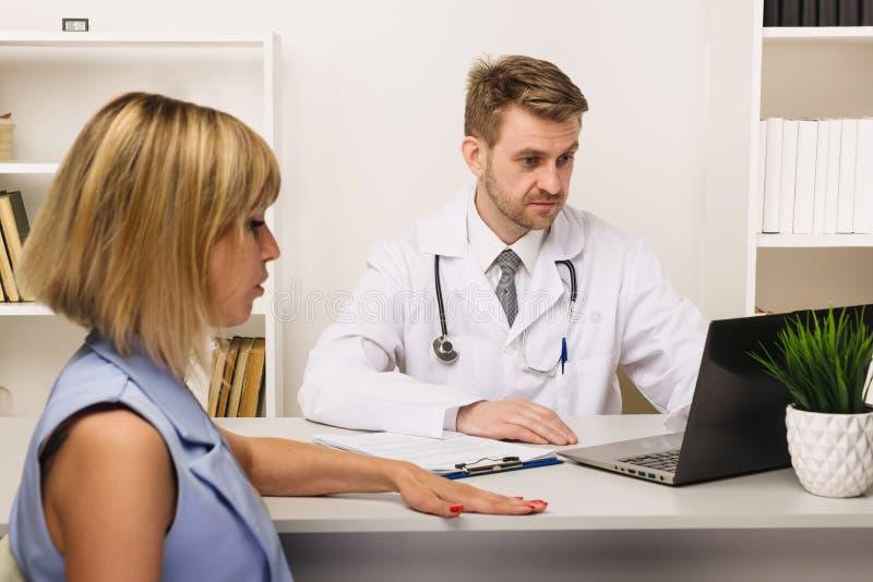 Junge Frau auf einer Beratung mit einem männlichen Chirurgen oder einem Therapeuten in seinem Büro lizenzfreie stockfotografie