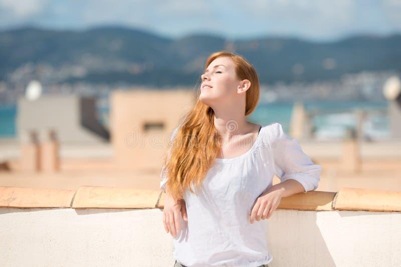 Junge Frau auf einer Dachspitzenterrasse stockfoto
