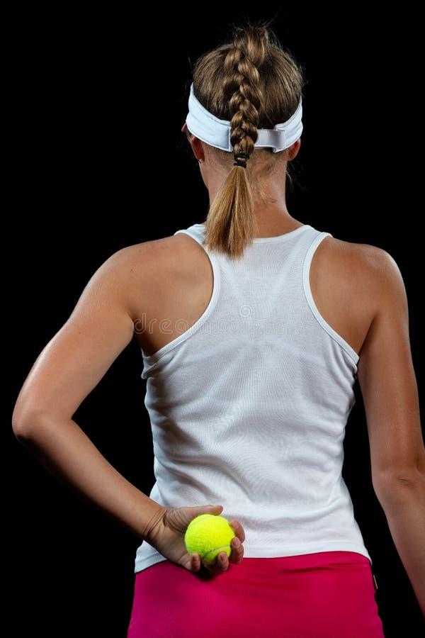 Junge Frau auf einer Tennispraxis Anfängerspieler, der einen Schläger, grundlegende Fähigkeiten lernend hält Portrait auf schwarz lizenzfreie stockfotos