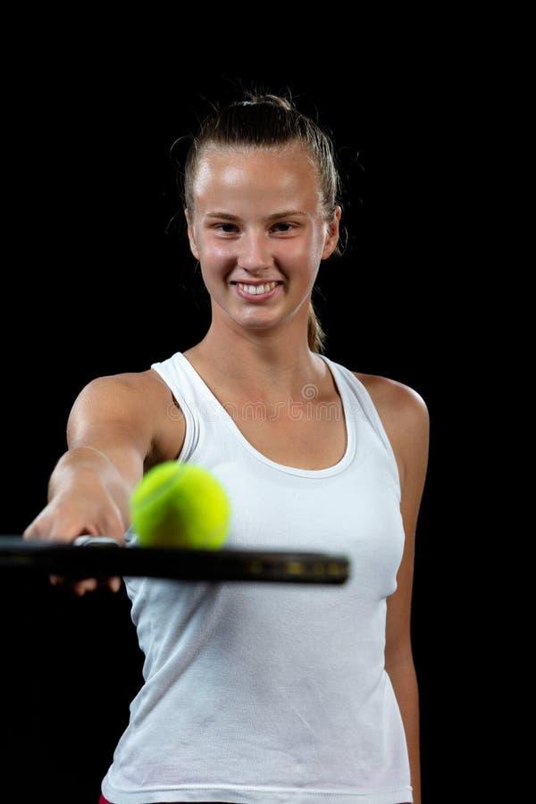 Junge Frau auf einer Tennispraxis Anfängerspieler, der einen Schläger, grundlegende Fähigkeiten lernend hält Portrait auf schwarz stockbild