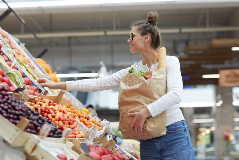 Junge Frau auf Frucht-Stand lizenzfreie stockfotografie