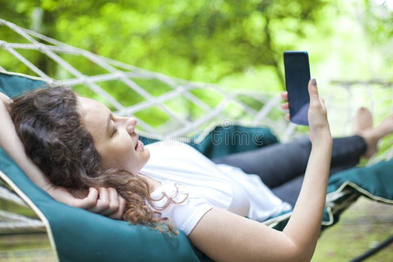 Junge Frau auf Hängematte unter Verwendung des Smartphone lizenzfreie stockfotografie