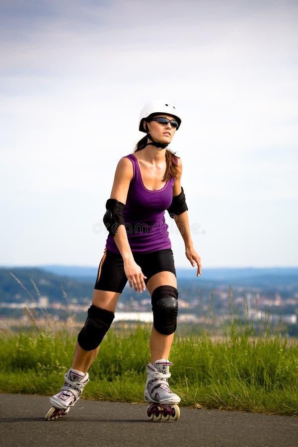 Junge Frau auf Rollerblades im Land stockfotografie