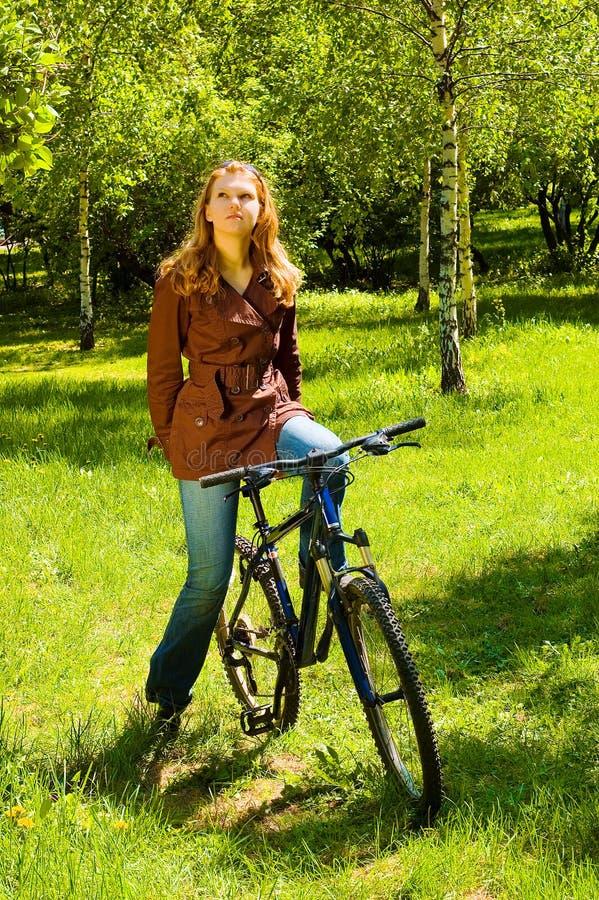 Junge Frau auf Wald des Fahrrades im Früjahr lizenzfreie stockbilder
