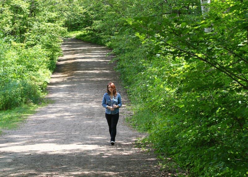 Junge Frau barfuß auf einem Waldweg lizenzfreie stockbilder