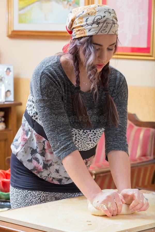 Junge Frau bearbeitet den Teig stockfoto