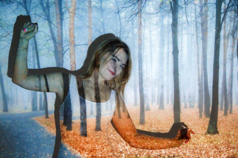 Junge Frau bedeckt mit dem Bild des Herbstwaldes lizenzfreies stockfoto