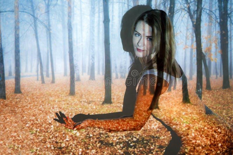 Junge Frau bedeckt mit dem Bild des Herbstwaldes stockfoto