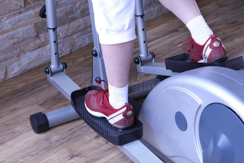 Junge Frau benutzt einen elliptischen Cross-Trainer in der Turnhalle lizenzfreies stockfoto