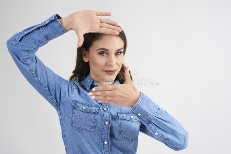 Junge Frau benutzt ihre Finger, um ihr Gesicht zu gestalten lizenzfreie stockfotografie