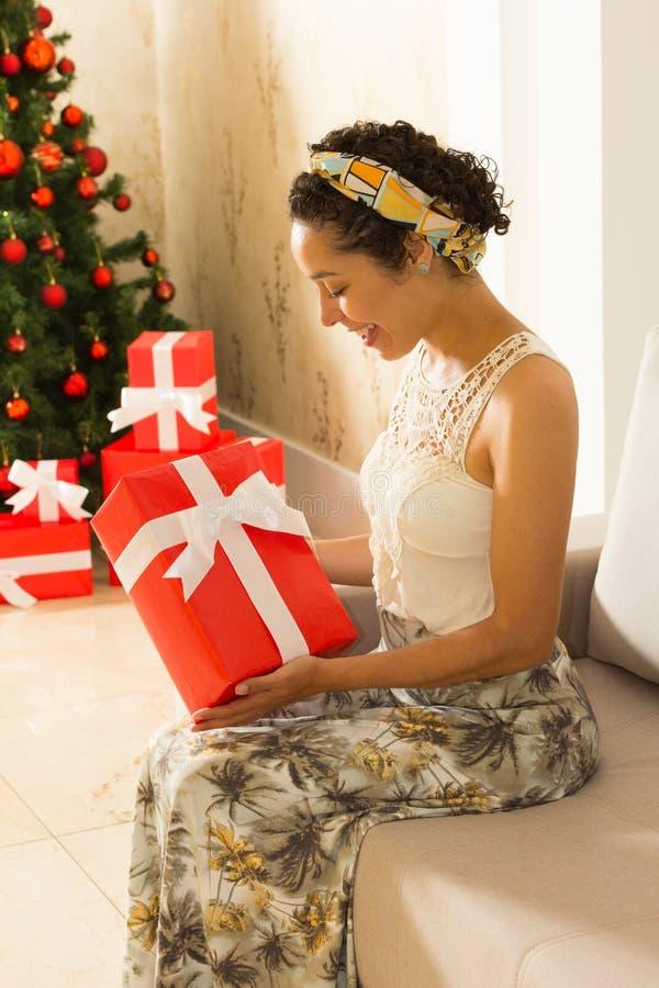 Junge Frau betrachtet ihr Weihnachtsgeschenk Roter Kasten und Chr stockfotos