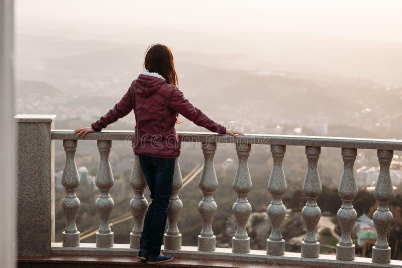 Junge Frau betrachtet von der Aussichtsplattform Stadt im Nebel stockbilder