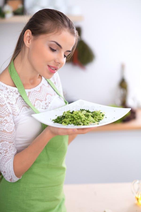 Junge Frau bietet frischen Salat beim Kochen in einer Küche an lizenzfreie stockbilder