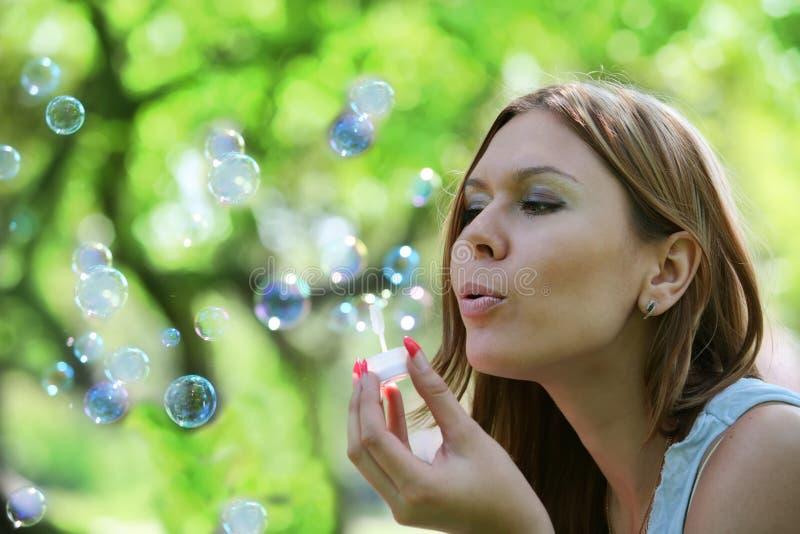 Junge Frau brennt Seifenluftblasen durch lizenzfreie stockbilder