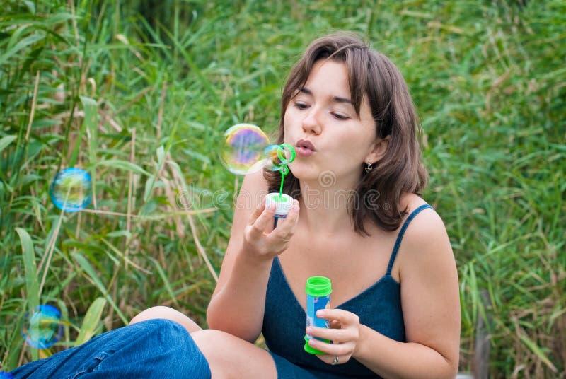 Junge Frau brennt Seifenluftblasen durch stockbild