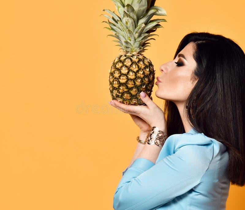 Junge Frau Brunette in der blauen offiziellen Abnutzungsjacke küsst eine Ananas auf gelbem Hintergrund lizenzfreies stockbild