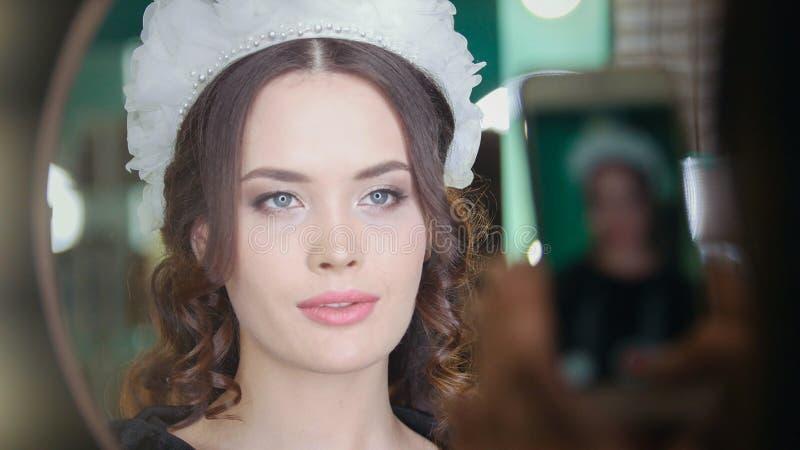Junge Frau Brunette in einem Schönheitssalon, der für Kamera aufwirft lizenzfreies stockfoto