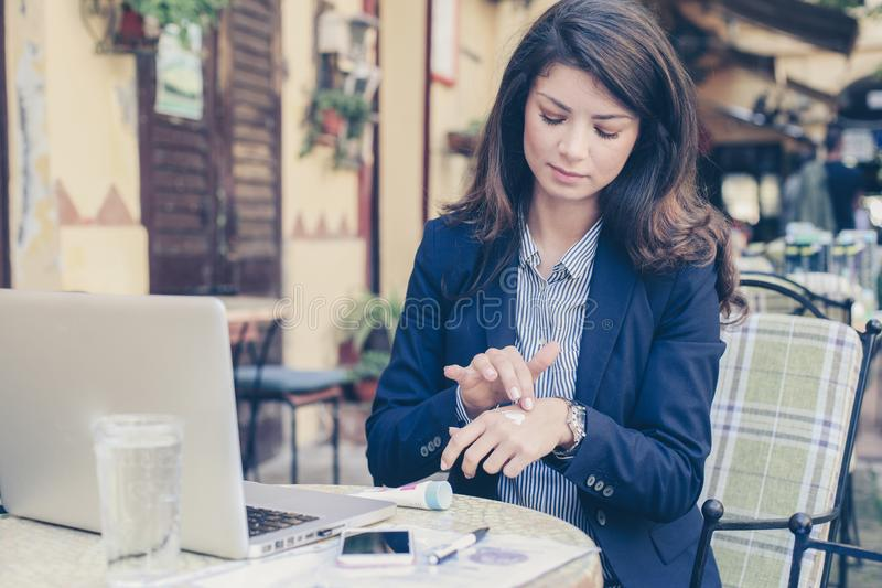 Junge Frau am Café unter Verwendung der Handcreme lizenzfreie stockbilder