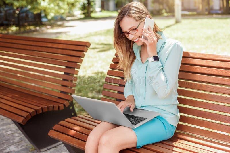 Junge Frau in den Brillen, die auf der Bank arbeitet an antwortendem Telefonanruf des Laptops auf froher Seitenansicht des Smartp stockfoto