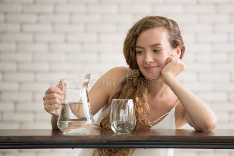 Junge Frau in den frohen Lagen mit Krug und Glas Trinkwasser stockfotografie