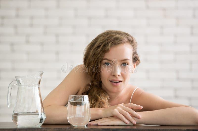 Junge Frau in den frohen Lagen mit Krug und Glas Trinkwasser stockfotos