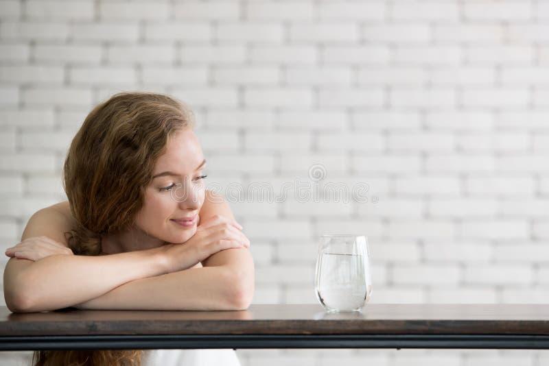 Junge Frau in den frohen Lagen mit Krug und Glas Trinkwasser stockfoto