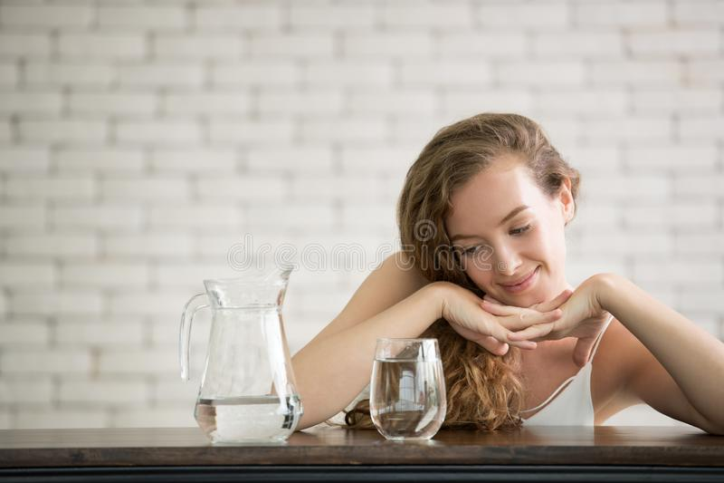 Junge Frau in den frohen Lagen mit Krug und Glas Trinkwasser stockbild