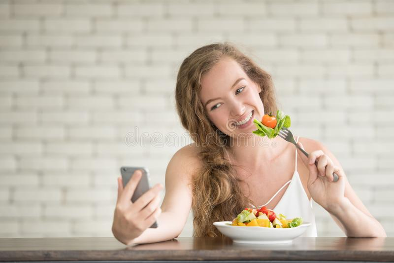 Junge Frau in den frohen Lagen mit Salatschüssel auf der Seite stockfoto